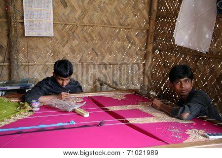 KUMROKHALI, INDIA - JAN 16: Indrajit, 17 and Anandalok, 15, Naskar working on the decoration of textiles in Kumrokhali, India on Jan 16, 2009.