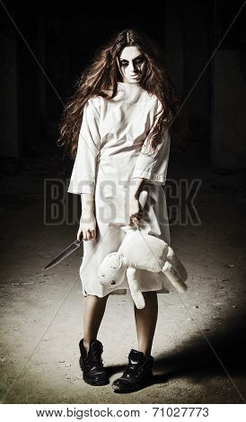 Horror scene: a scary monster girl with moppet doll and knife in hands poster