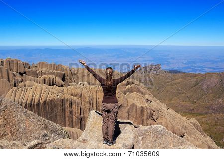 Young Woman On Edge Of The Mountain Looking At Horizon