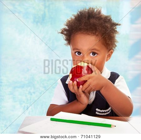 Portrait of cute little African boy sit behind a desk and biting big red apple, drawing using green pencil, having lunch in classroom, happy preschooler concept