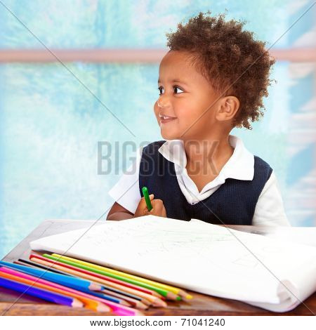 Portrait of cute little African preschooler on drawing lesson, painting with many colorful pencils, elementary education concept