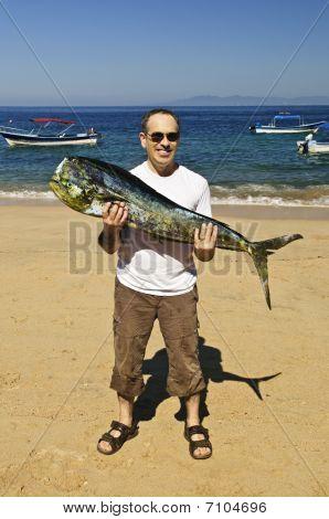 Tourist Holding Big Fish On Beach