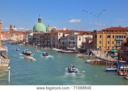 VENICE, ITALY - SEPTEMBER 9, 2010: Elegant, carefree tourists on the vaporetto and gondola on Grand Canal.  Sunny Day