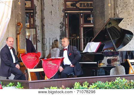 Musicians On The Terrace Under The Canopy Of The World Famous Cafe Florian In Piazza San Marco In Ve