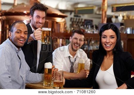 Happy friends having fun in pub watching sport in TV together drinking beer cheering for team.