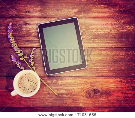 a tablet with a cup of coffee and a flower on a wooden texture background toned with a retro vintage instagram filter  poster