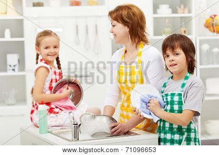 Kids and their mother washing dishes in the kitchen