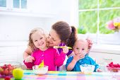 Happy young family mother with two children adorable toddler girl and funny messy baby boy having healthy breakfast eating fruit and dairy sitting in a white sunny kitchen with window poster