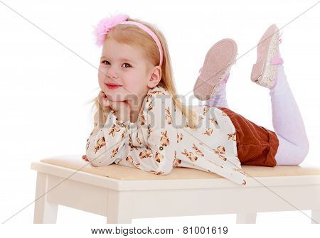 Adorable little girl lying on the banquette.