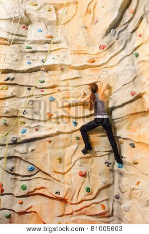 Woman climbing on man-made cliff in the sport centre poster