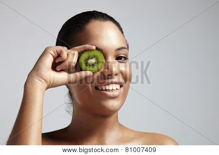 Happy  Girl With A Kiwi Slice Close To Her Eye