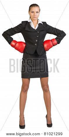 Businesswoman wearing boxing gloves standing akimbo