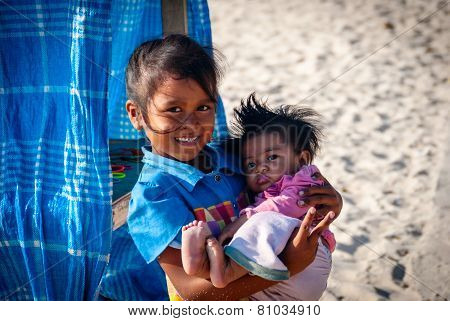 Young Balinese Girl Holding Her Brother