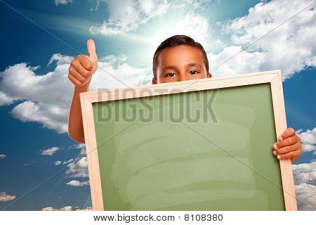 Proud Hispanic Boy Holding Blank Chalkboard Over Sky