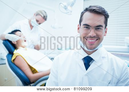 Portrait of smiling male dentist with assistant examining womans teeth in the dentists chair poster