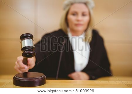 Serious judge with a gavel wearing robes and wig in the court room