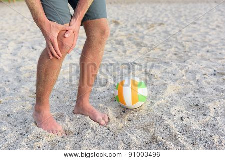 Injuries - sports knee injury on man playing beach volleyball. Male beach volley ball player with pain, maybe from sprain knee. Close up of legs, muscle and knee outdoors.