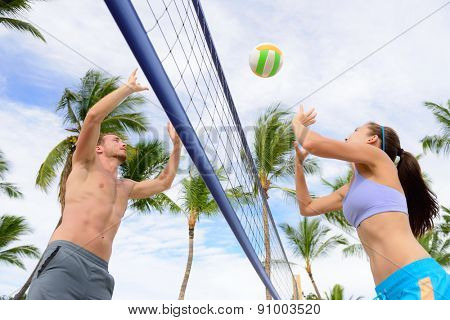 Friends playing beach volleyball sport. Woman and man having fun recreational volley ball game in summer living healthy active sport lifestyle.