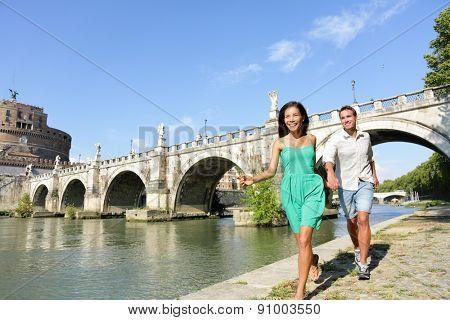Romantic couple tourists walking Castel Sant Angelo, Rome. Happy romantic couple looking at the roman castle enjoying their romantic summer holiday travel in Italy, Europe. Man and woman holding hands
