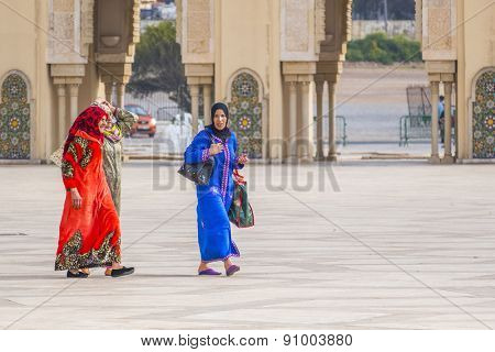 CASABLANCA, MOROCCO, APRIL 2, 2015:  Local women in traditional attire walk the outside grounds of Hassan II Mosque or Grande Mosquee Hassan II