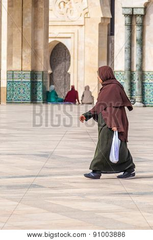 CASABLANCA, MOROCCO, APRIL 2, 2015: Local woman in traditional attire walks on the outside grounds of Hassan II Mosque or Grande Mosquee Hassan II