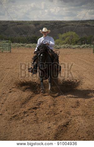 Cowboy Running Toward On A Black Horse