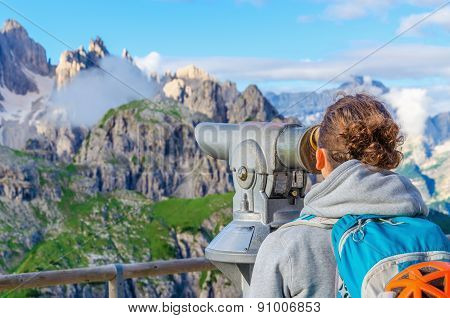 Young woman with binoculars in Dolomites, Italy