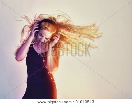A girl is listening to music on her headphones and her hair is blowing wild on a white background for an entertainment or rock concept.
