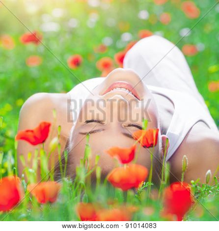 Beautiful young girl lying down on fresh poppy flower field, closing eyes of pleasure, enjoying amazing spring time sunny day
