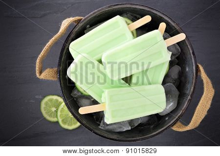 Homemade Lime Yogurt Popsicles In A Rustic Ice Filled Tin Pail Against A Slate Background