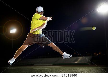 Tennis player hitting the ball at night