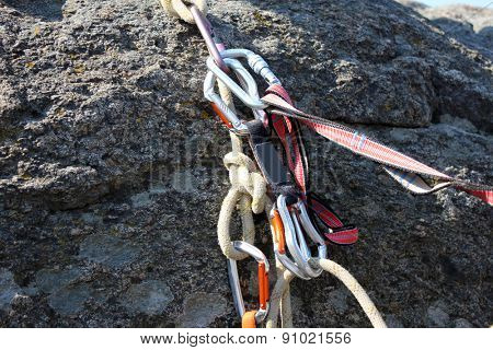 Rock climbing rope with hooks on  rock, close-up