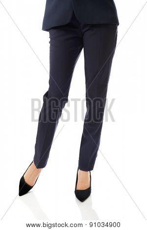 Close up on businesswoman slim legs in high heels standing astride.