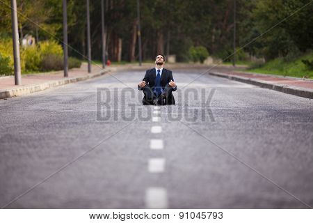 Businessman meditating sit in the middle of the street