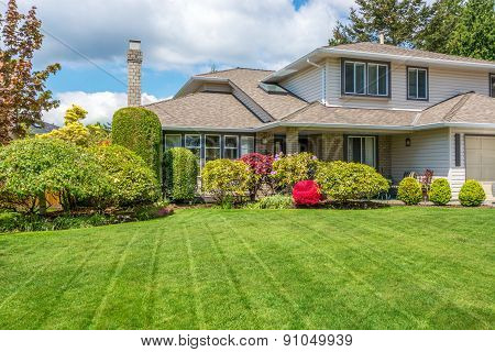 Luxury house with freshly mown grass lawn. Home exterior.