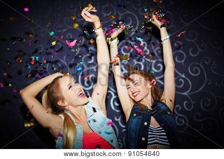 Two energetic girls dancing in night club