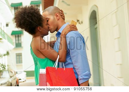 African American Couple Shopping With Credit Card Kissing