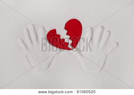 Broken red heart with hand prints in the sand for love sickness concepts.