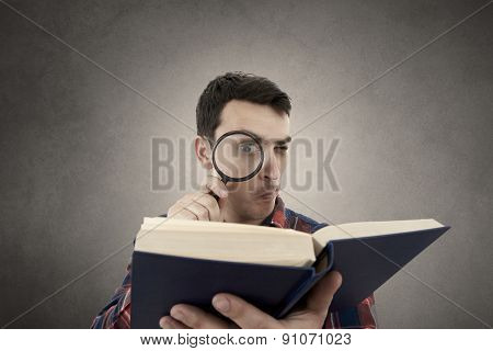 Curious young student man holding book with a magnifying glass.