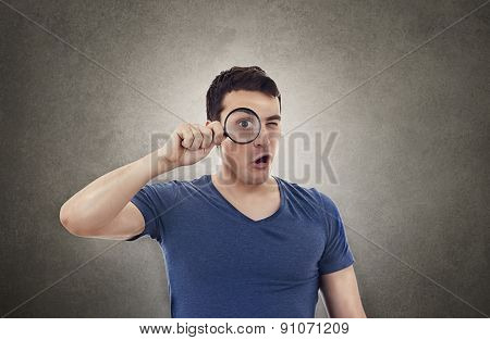 Perplexed Surprised Young man student holding magnifying glass isolated over grey background.