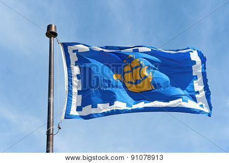 The flag of Quebec City waving in the wind. This flag was officially adopted by the city in 1987. On the flag the yellow ship of the founder Samuel de Champlain and the crenelated white border represents the fortified city walls. Quebec City Quebec Canada