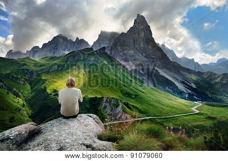 The young man is resting on the rock after hiking trip, he is looking to green mountains meadows under towering hill in italian Dolomite. poster
