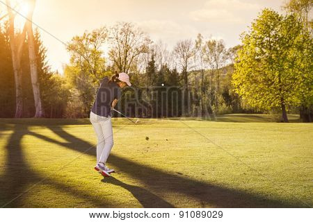 Woman golf player swinging golf club on fairway at beautiful sunset.