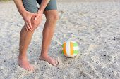 Injuries - sports knee injury on man playing beach volleyball. Male beach volley ball player with pain, maybe from sprain knee. Close up of legs, muscle and knee outdoors. poster