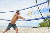 Beach volleyball man playing forearm pass hitting volley ball during game on summer beach. Male model living healthy active lifestyle doing sport on beach. poster