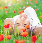 Beautiful young girl lying down on fresh poppy flower field, closing eyes of pleasure, enjoying amazing spring time sunny day poster