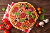 Italian pizza with pepperoni, tomatoes, olives and basil on wooden table. Top view  poster