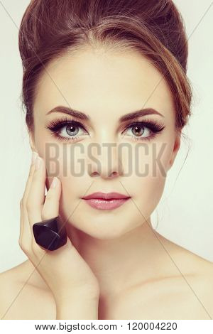 Vintage style portrait of young beautiful stylish girl with hair bun and winged eyes make-up