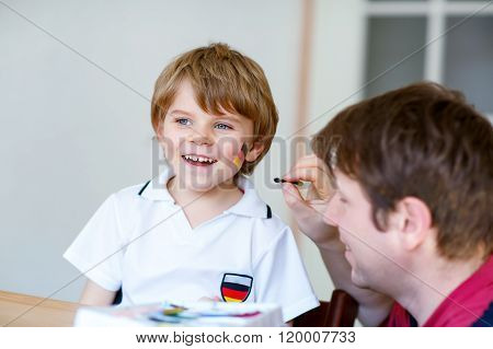 Father painting flag on face of little kid for football or socce
