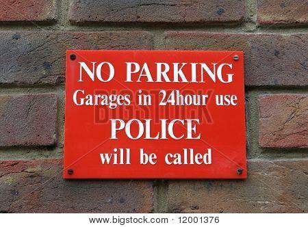 No Parking sign on brick wall